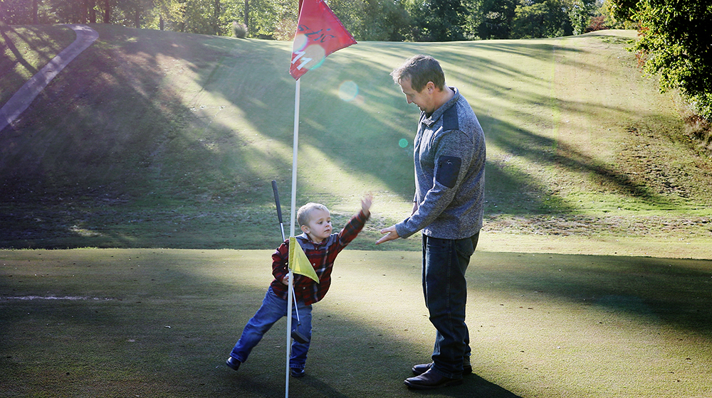 The Rustic Golf Course father and son high five the rustic golf course