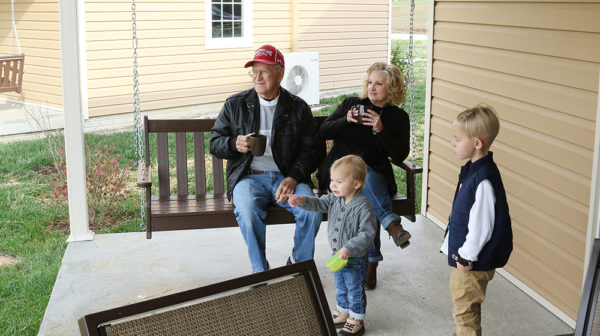 Grandparents and grandchildren on porch swing at cottage