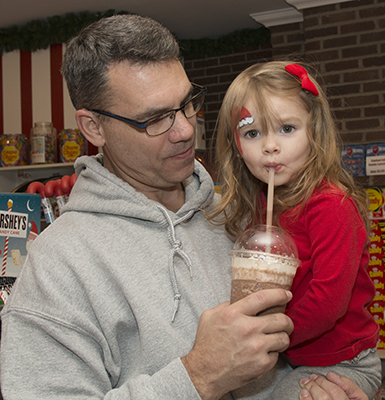 Father and daughter enjoying frozen hot chocolate at Santa's Candy Castle