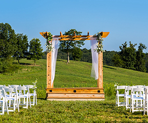Decorated wedding trellis and white chairs on grassy hill at Matilda's Event Barn