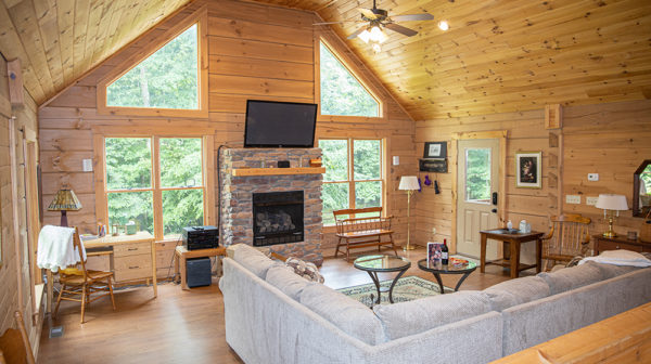 Hollow Creek Cabin vacation rental living room with sectional, fireplace, and large windows overlooking trees