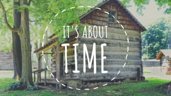 """Summer scene of log cabin with covered front porch at Lincoln Pioneer Village and the words """"it's about time"""""""