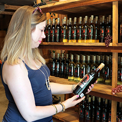 Woman standing in front of wine on shelves at Pepper's Ridge Winery and holding a bottle of wine