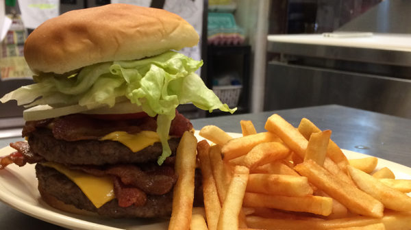 Close up of a double burger with cheese, bacon, lettuce, onion and a side of fries
