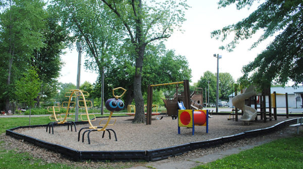 Playground equipment at community park in Dale, Indiana, with green trees in background