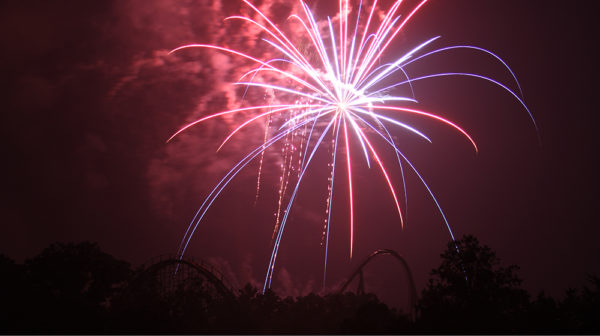 Red, white, and blue fireworks display lighting up dark sky with Holiday World roller coaster in background