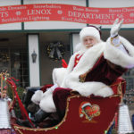 Santa Claus sits in his sleigh during a parade and waves toward the camera