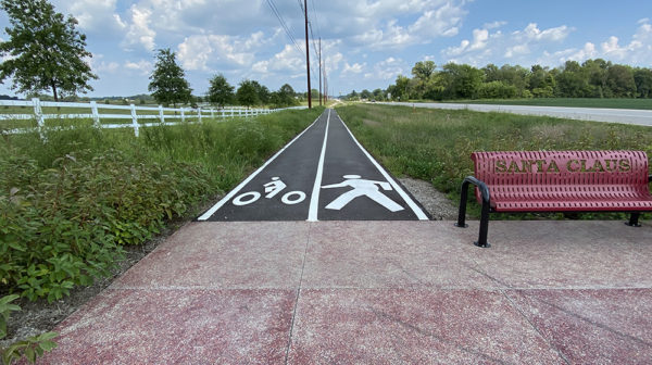 Entrance to a paved walking trail with white painted line down center and symbol for biking on left and symbol for walking on right. Grace is on either side of path and red bench sits to the right.