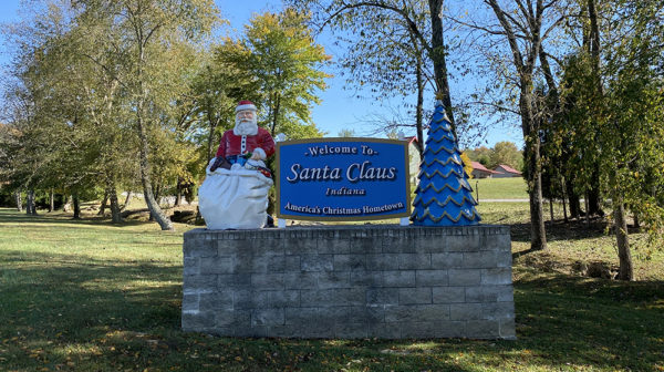 Large sign located at Santa's Lakeside Cottages features Welcome to Santa Claus placard with Santa statue on one side and tree on the other